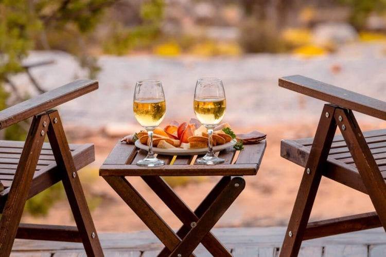 Wine glasses sit on a table between lounge chairs on the yurt deck at Mill Creek Ranch Resort.